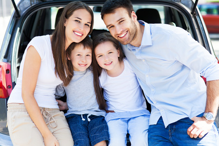 two parents: Happy family of four sitting in car trunk  Stock Photo