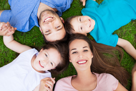 four people: Family outdoors lying on grass