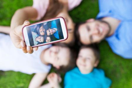 papa y mama: Familia que toma imagen de s� mismos con el tel�fono inteligente Foto de archivo