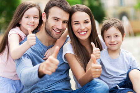 women having fun: Family showing thumbs up Stock Photo
