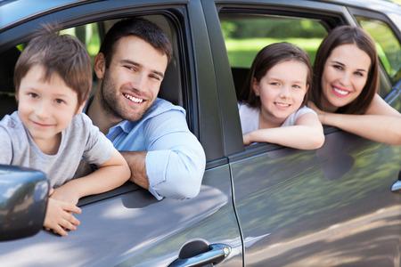 familias jovenes: Familia feliz que se sienta en el coche