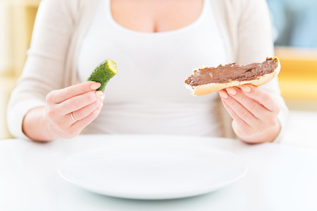 Pregnant woman with pickle and chocolate sandwich photo