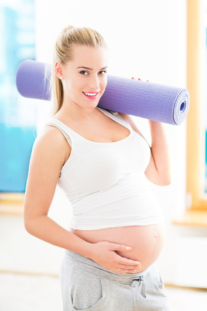 Pregnant woman holding yoga mat photo