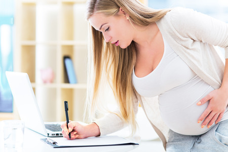 working people: Schwangere Frau bei der Arbeit