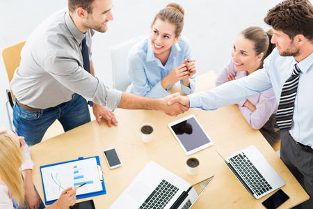 young business: Business people shaking hands across table