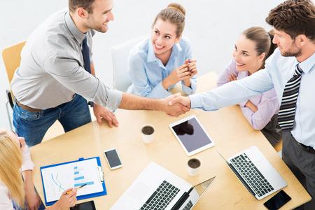 reuniones empresariales: La gente de negocios d�ndose la mano a trav�s de la mesa
