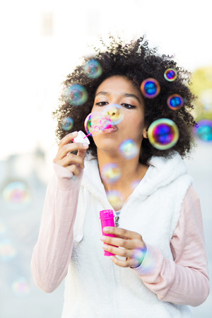bubbles: Afro woman blowing soap bubbles