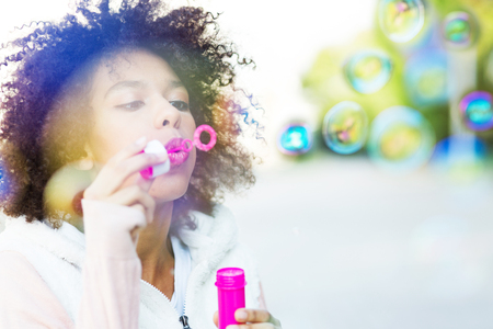 Afro woman blowing soap bubbles photo