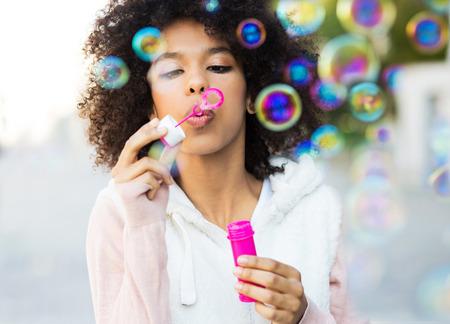 positivity: Afro woman blowing soap bubbles