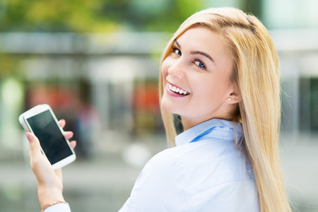 Young woman holding mobile phone photo