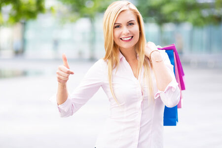 Woman with shopping bags showing thumbs up photo