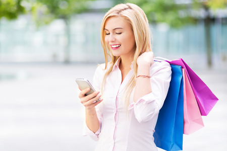 mobile shopping: Woman with shopping bags and mobile phone Stock Photo