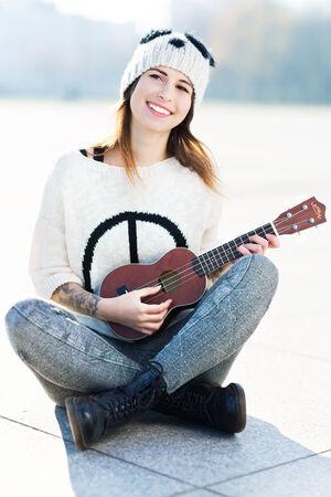 wolly: Young woman playing ukulele