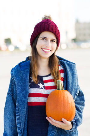 wolly: Young woman holding a pumpkin