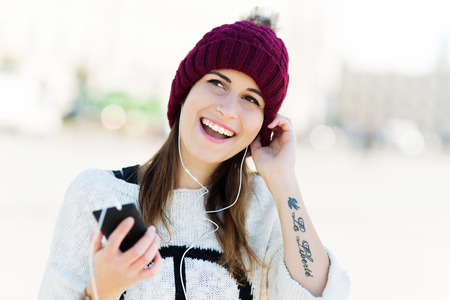 wolly: Girl listening to music on smartphone Stock Photo