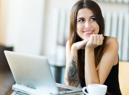 Tattooed woman using laptop at cafe photo
