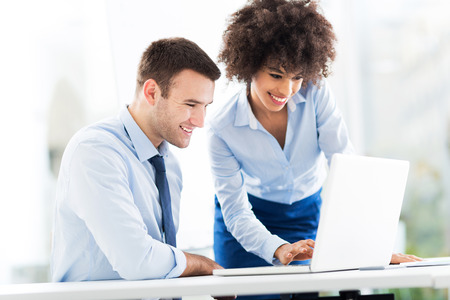 Business people using laptop together Stock Photo