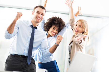 Business people cheering with arms raised photo