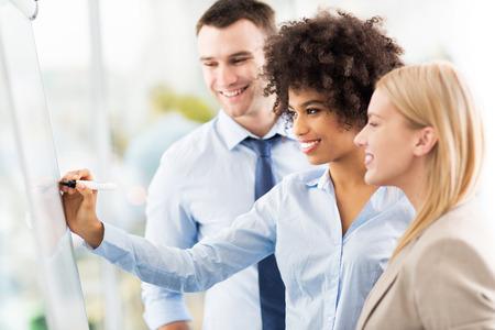 reuniones empresariales: Empresarios que escriben en el rotafolio Foto de archivo