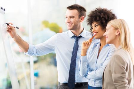 Businesspeople writing on flipchart Standard-Bild