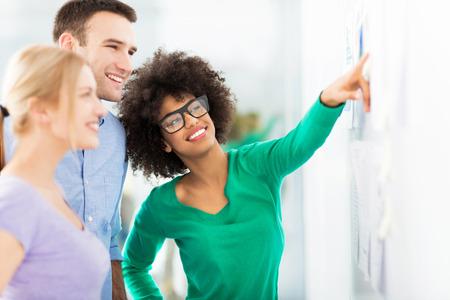 Jonge mensen uit het bedrijfsleven bespreken op zelfklevende notities