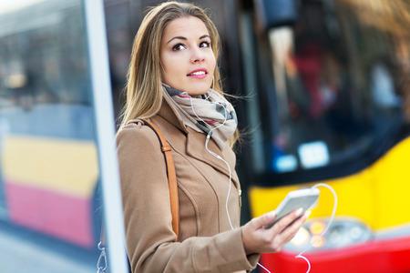 Frau wartet an der Bushaltestelle