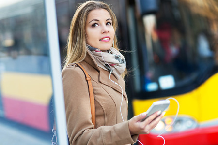 smartphones: Woman Waiting at Bus Stop