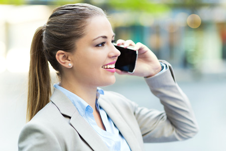 holding cell: Young businesswoman with mobile phone Stock Photo
