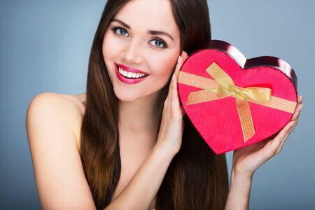 Woman holding heart-shaped box photo