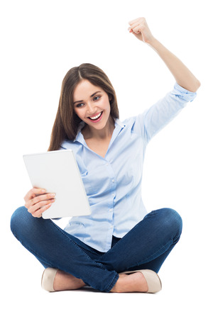 clenching fists: Excited woman looking at digital tablet Stock Photo