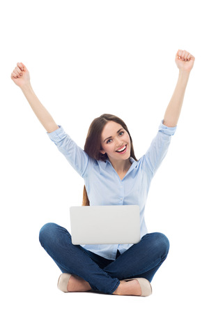 clenching fists: Woman raising arms in front of her laptop Stock Photo