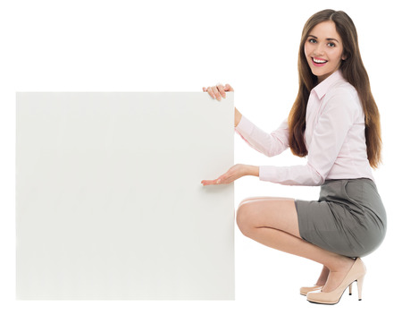Woman crouching next to blank board photo