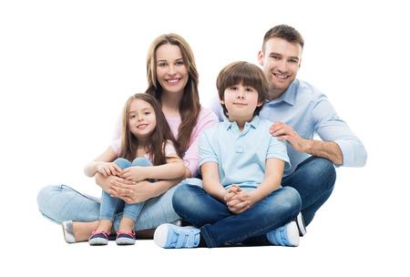 familias jovenes: Familia joven con dos niños sentados juntos Foto de archivo