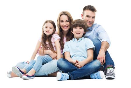 famille: Jeune famille avec deux enfants assis ensemble