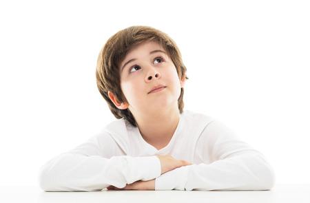 Jongen aan de tafel zitten omhoog te kijken Stockfoto