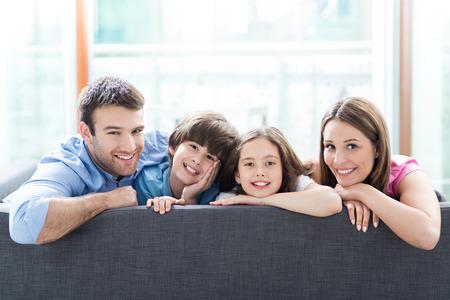 relajado: Familia que se sienta en el sof� Foto de archivo