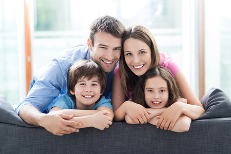 familias jovenes: Familia que se sienta en el sofá Foto de archivo