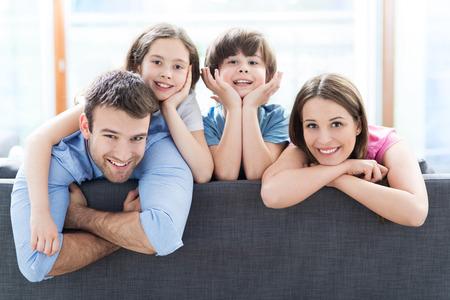 pareja enamorada: Familia que se sienta en el sof� Foto de archivo