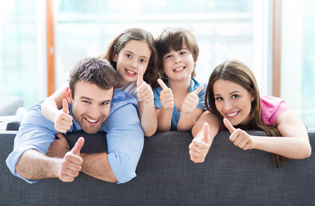 family with two children: Family at home with thumbs up Stock Photo