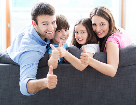 family sofa: Family at home with thumbs up Stock Photo