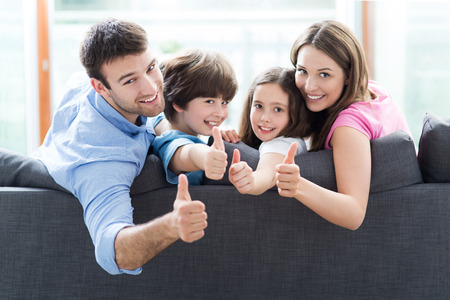 resting: Family at home with thumbs up Stock Photo