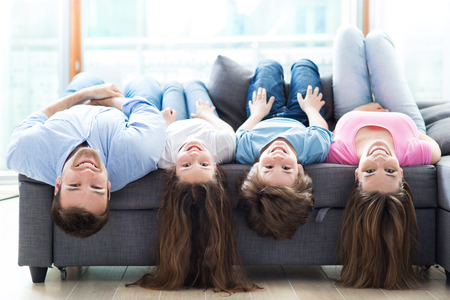 Family lying upside down on sofa