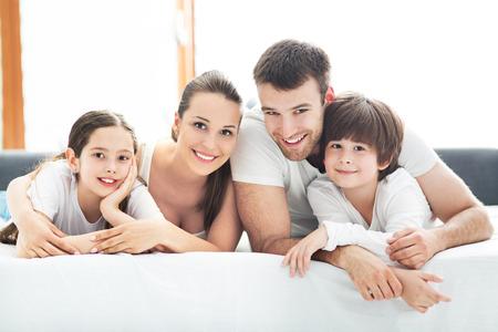 ベッドの上に横たわる四人家族