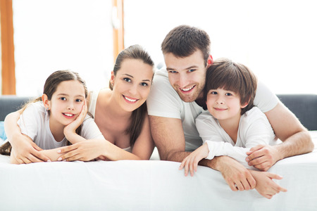 wife: Family of four lying on bed Stock Photo