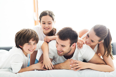 girl bed: Family of four lying on bed Stock Photo