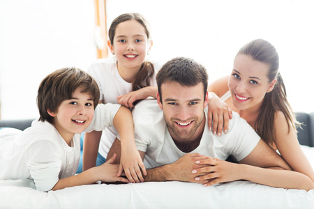 Smiling family lying together on bed Imagens