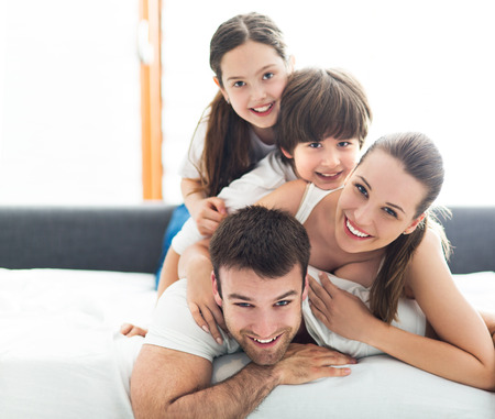 wives: Smiling family lying together on bed Stock Photo