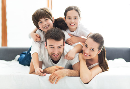 Smiling family lying together on bed Foto de archivo