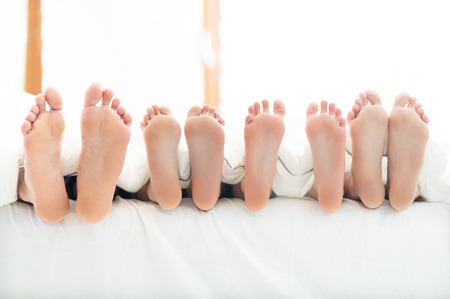 adult foot: Feet of family in bed