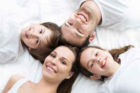 Family of four lying on bed Imagens